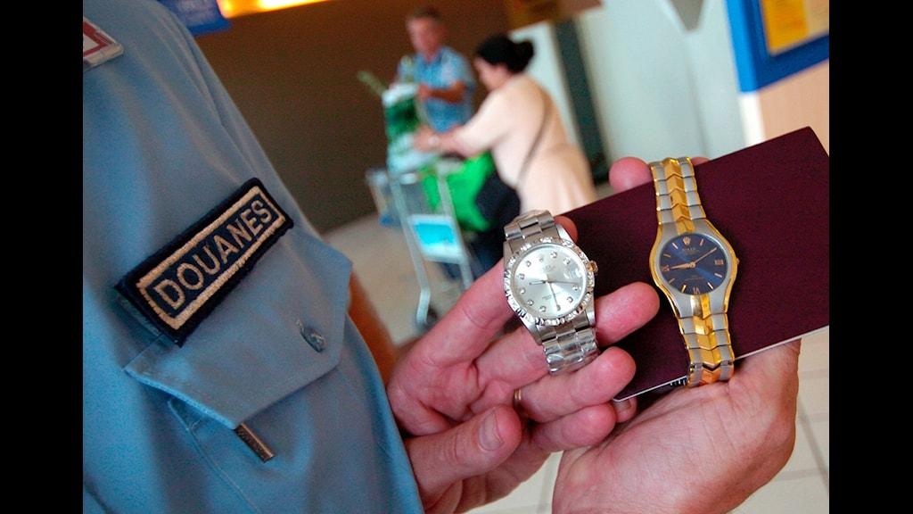 En bild på en hand som håller två klockor brevid varandra