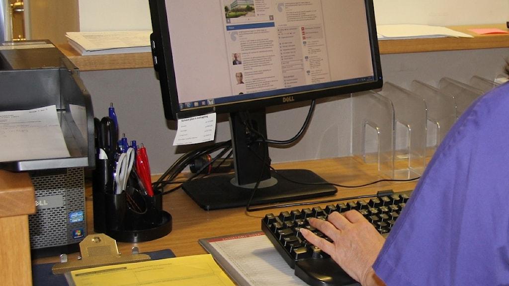 Sjuksköterska sitter framför en dator