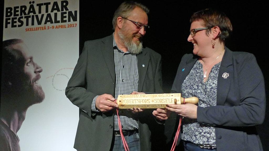 Nordmalings kommunalråd Madelaine Jakobsson överräcker berättarkaveln till Kommunfullmäktiges ordförande i Sorsele Roland Wermelin