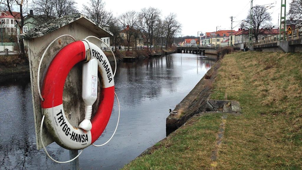 En livboj hänger bredvid en å.