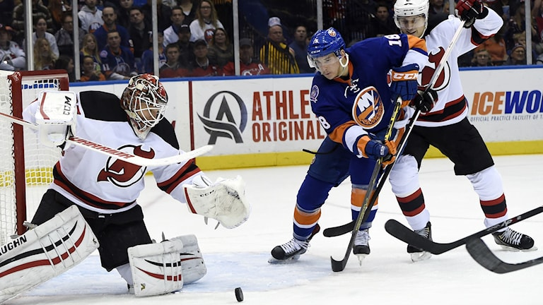 New Jersey Devils goalie Cory Schneider, left, blocks a shot on goal by New York Islanders center Ryan Strome (18) as Devils defenseman Adam Larsson (5) defends in the second period of an NHL hockey game at Nassau Coliseum on Saturday, Nov. 29, 2014, in Uniondale, N.Y. AP Photo/Kathy Kmonicek
