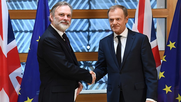 Britain's ambassador to the EU Tim Barrow (L) shakes hands with European Council President Donald Tusk.
