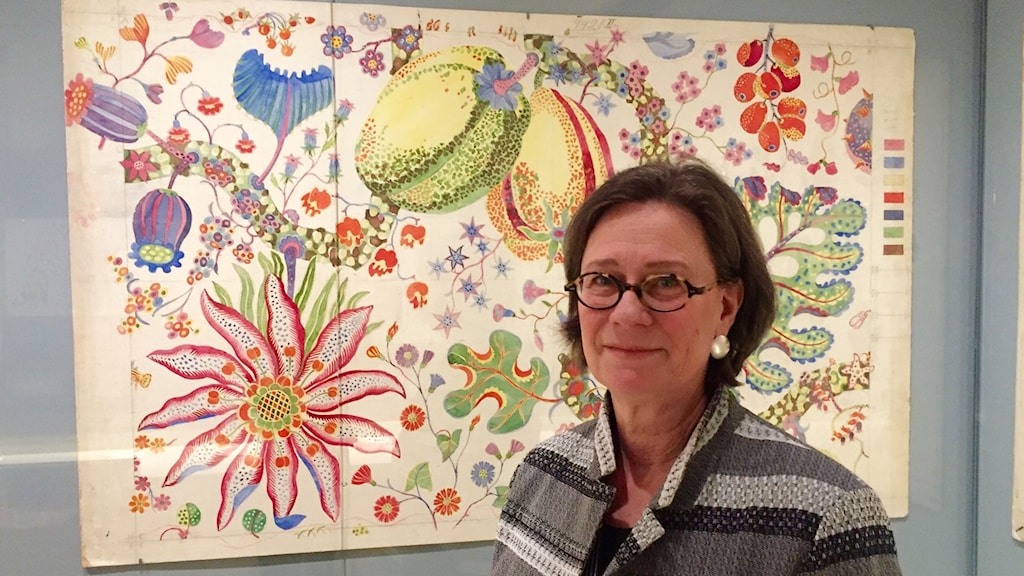 Karin Årberg Waern, the head of exhibitions at ArkDes, in front of a brightly-colored, floral original watercolor sketch by Josef Frank.
