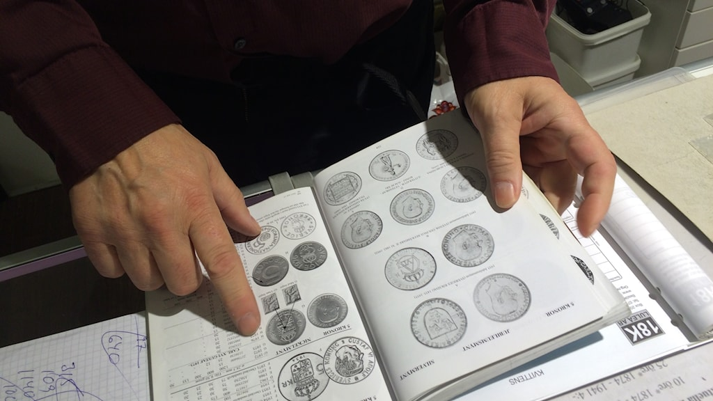 Book showing old coins. Hands holding the book.