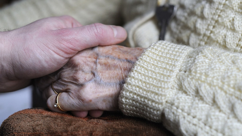 Close up on a hand holdning the hand of an older woman - she has a white sweater and a diamond ring on her pinky. Photo: Sebastien Bozon/TT