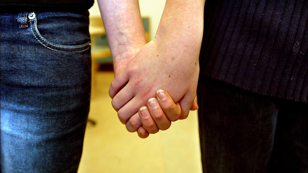 A Swedish man and a woman holding hands.