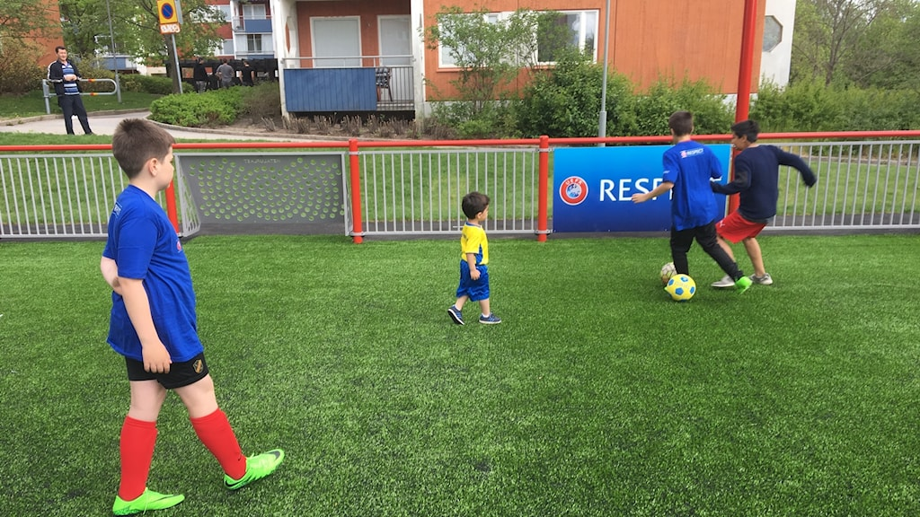 Two year old Alvin is the first to kick a ball on the new artificial pitch in Husby which was donated by UEFA as part of Stockholm hosting the Europa League final.