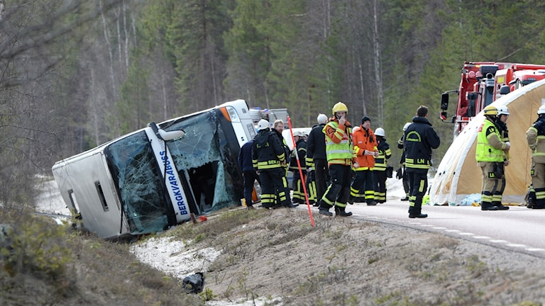 The double decker bus lying on the side of the road, with rescue staff around it.