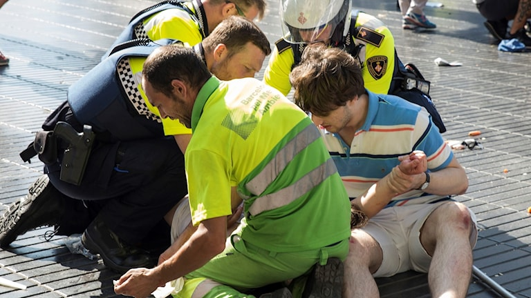 Spanish policemen help someone injured in the attack.