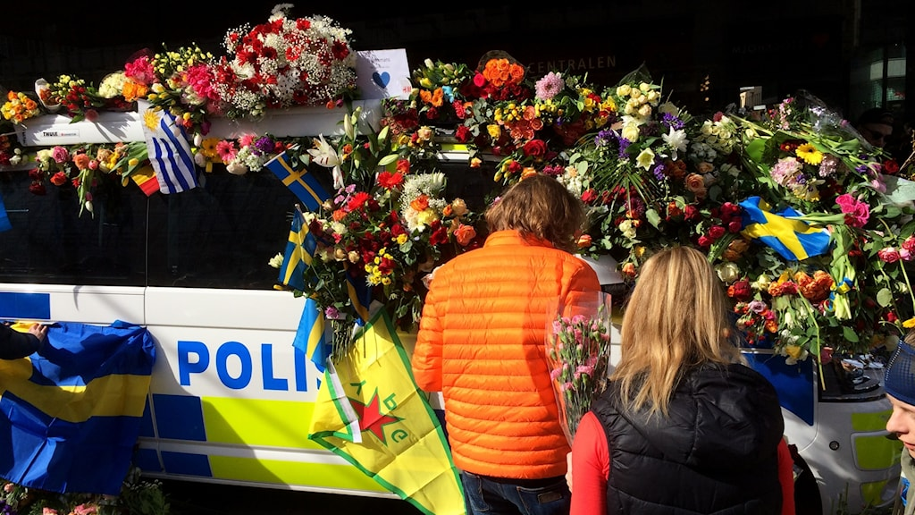 Passers-by covered a police car with flowers