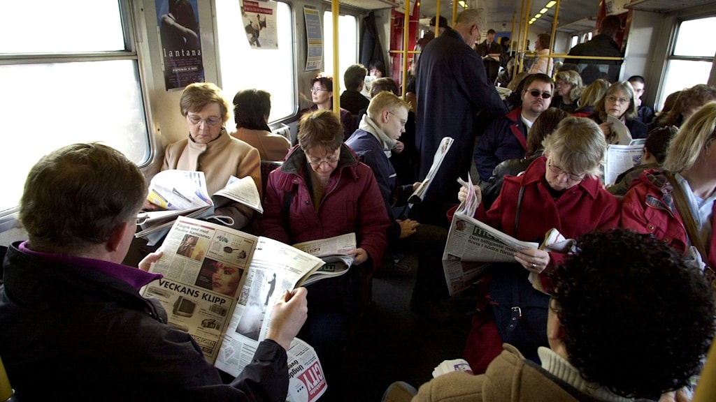 Commuters read newspapers on a train.