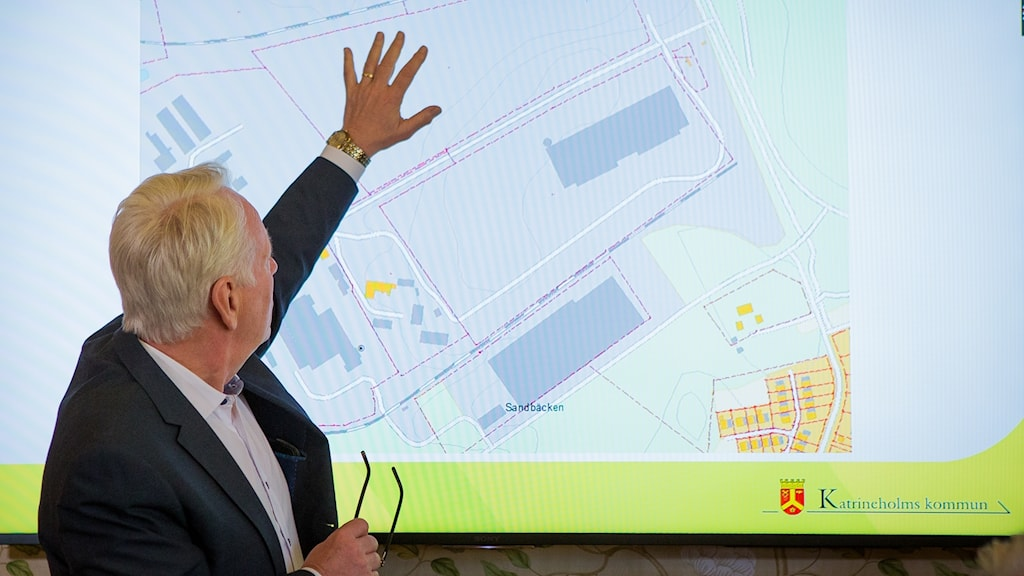 Katrineholm Mayor Göran Dahlström in front of a map of the area.
