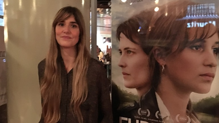 Woman next to a film poster portraying two women.
