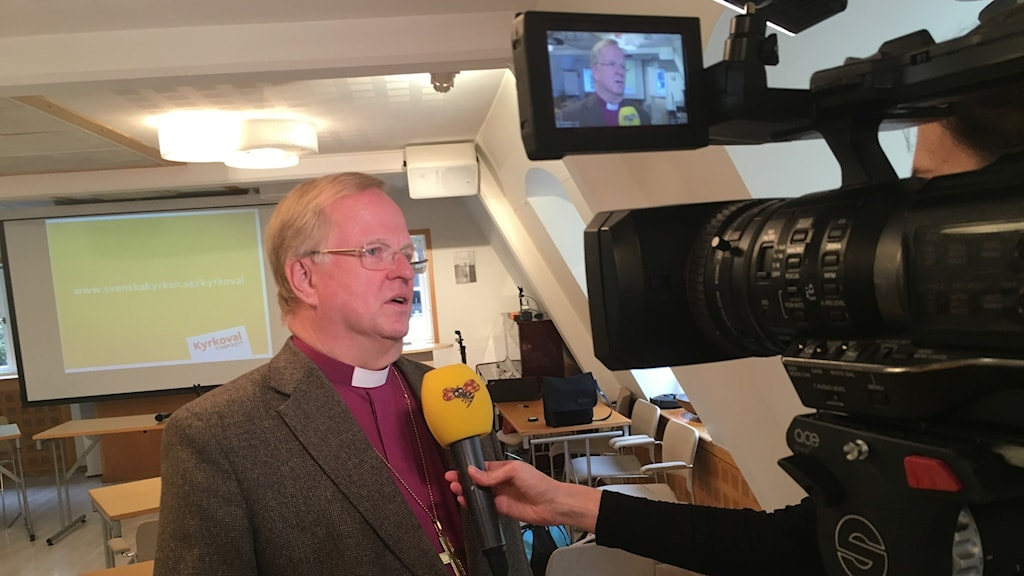 Man with a priest's collar interviewed in front of a camera.