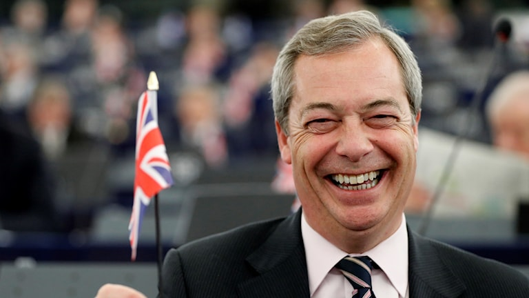 Nigel Farage laughing and holding a British Union Jack flag.
