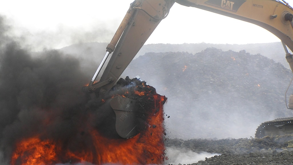 Grävskopa med glödande kol