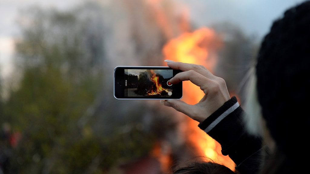 A meeting of the old and the new, as a Swede records a Valborg fire on a smartphone.