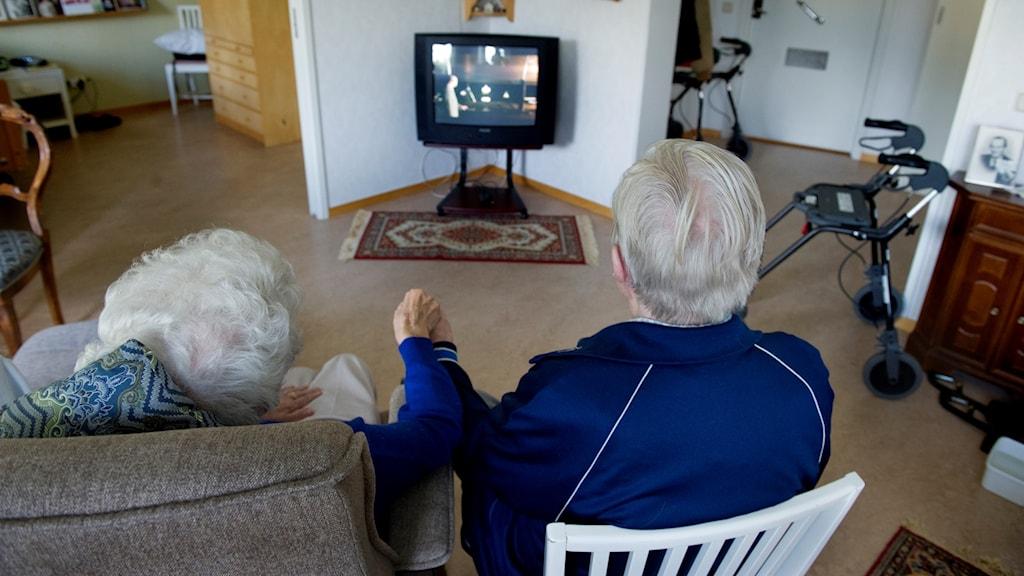 Två äldre personer som tittar på tv.