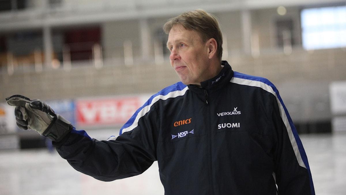 Suomen jääpallomaajoukkueen valmentaja, Antti Parviainen, osoittaa jonnekin oikealla kädellään.