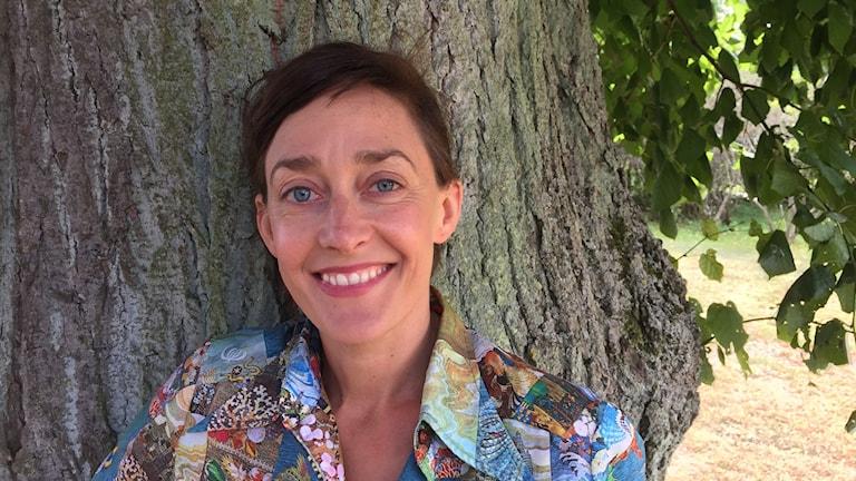 Kvinna med mörkt hår står framför en trädstam.