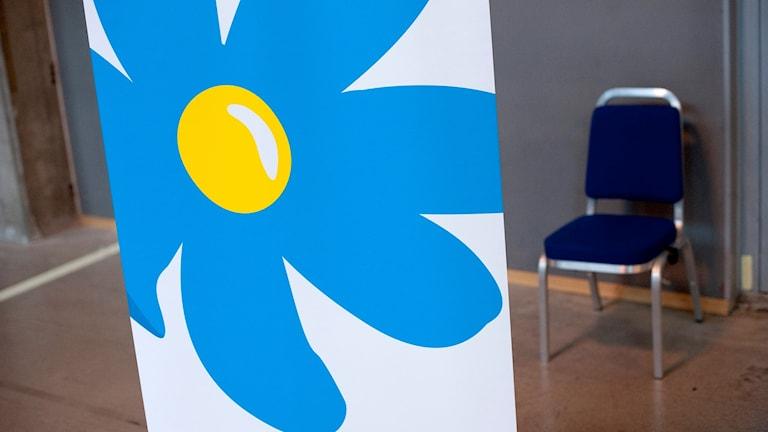 Sverigedemokraternas stora logga och en tom stol i bakgrunden.