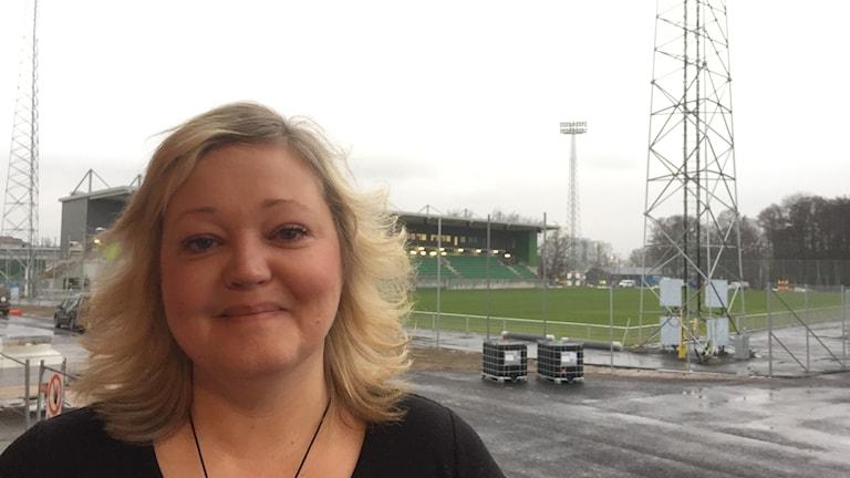 Blond kvinna framför fotbollsplan.