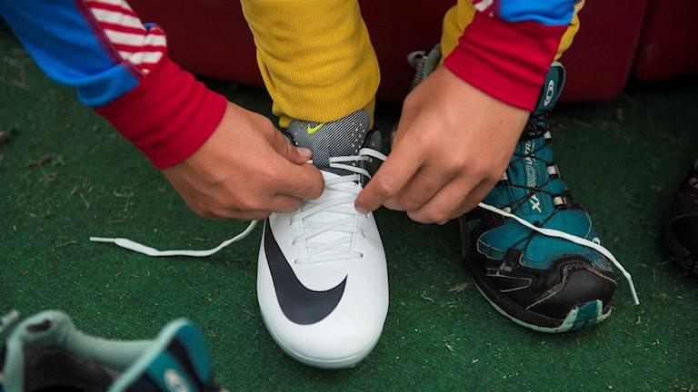 Ung människa knyter fotbollsskor.