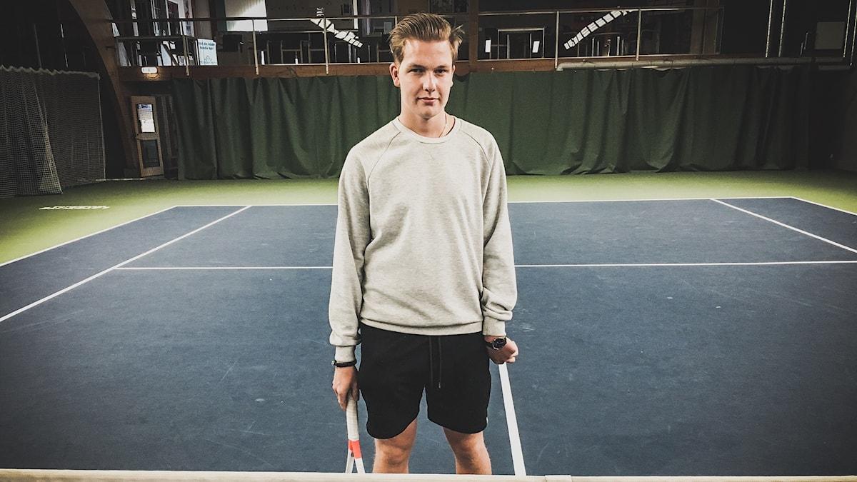 Elof Zetterberg står mitt på tennisplanen och tittar in i kameran.