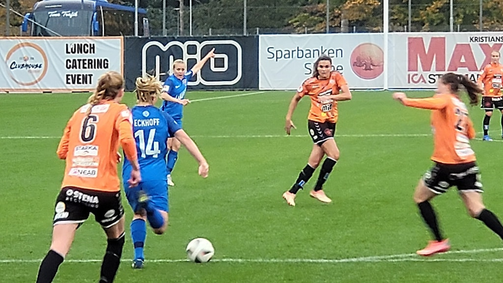 Sex fotbollspelare i spel på gräsplan.