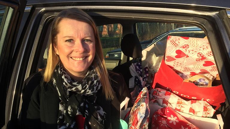 Kvinna med julklappar i bilen