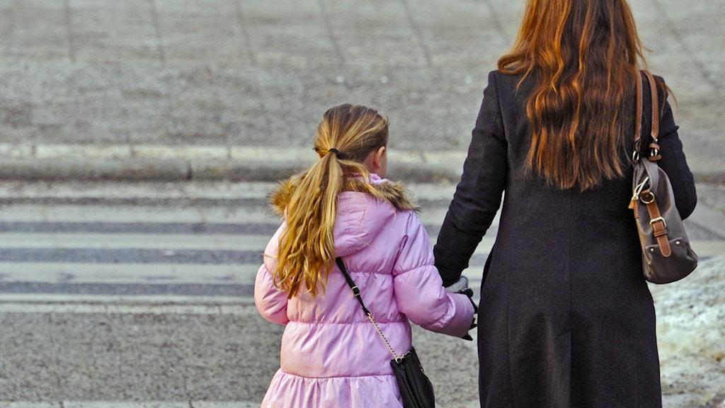 Mamma och dotter går över övergångsställe.