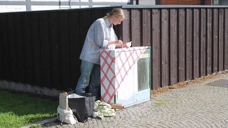 Karin Palola målar ett elskåp vid Rosentorget.