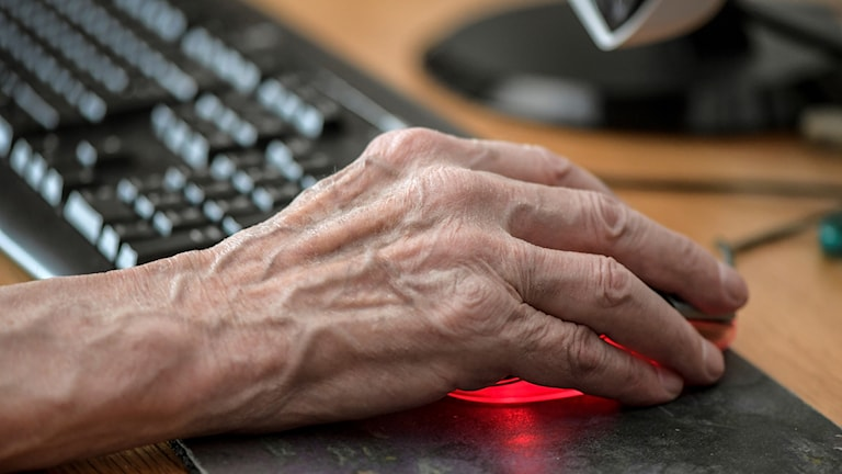 En gammal hand vid dator.