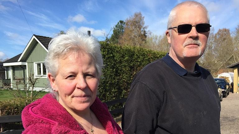 Kvinna i rosa jacka och man med solglasögon står i ett villaområde.