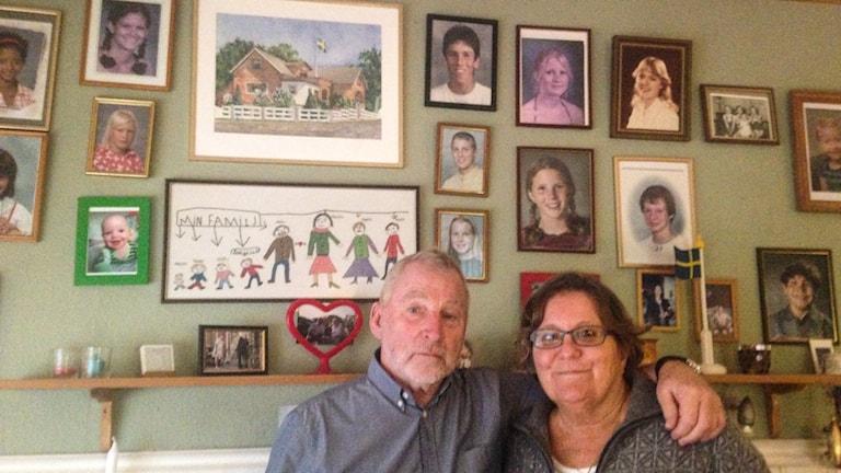 En man och en kvinna framför en vägg av porträttfoton