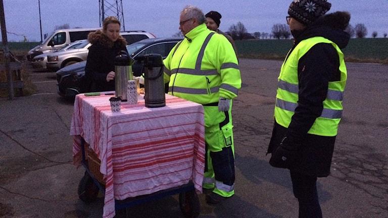 Christer Szakos och Emma Nilsson från styrelsen på Hammenhögs friskola delar ut kaffe till föräldrar på morgonen för att de ska lämna barnen på en säker parkering.