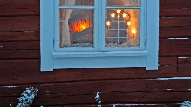 Fönster med adventsljusstake och snö utanför.