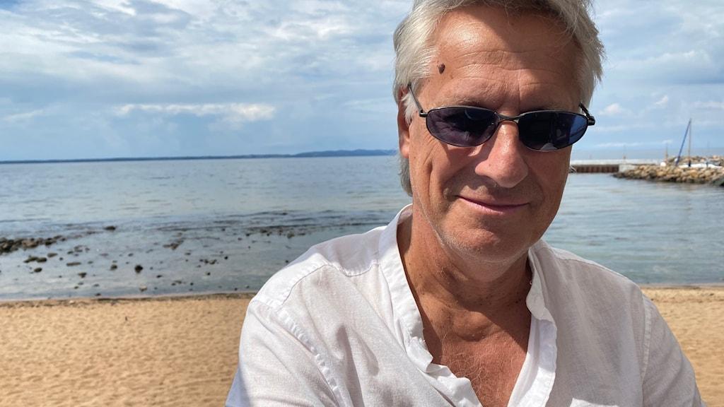 Man med grått hår och glasögon på strand.