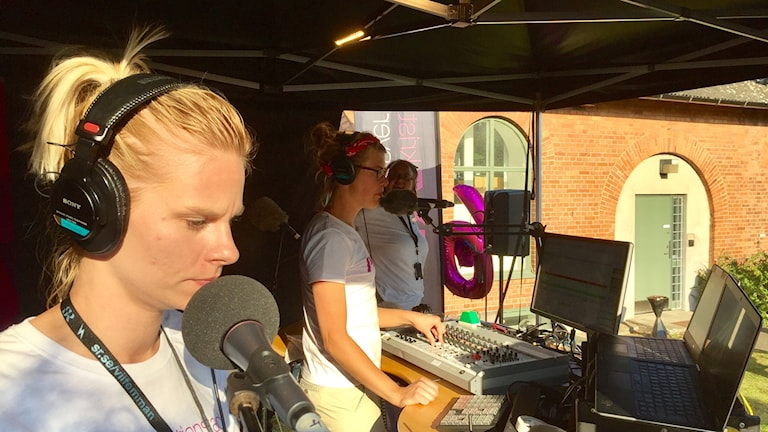 Tre kvinnor i en studio på en scen.