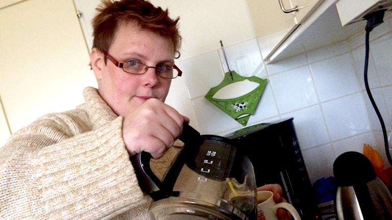 En kvinna häller upp en kopp kaffe.