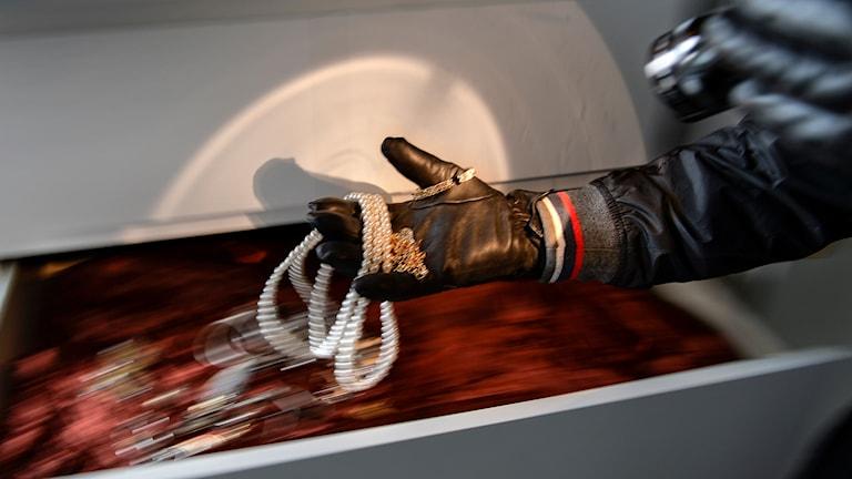 Hand som tar smycken ur en byrålåda.