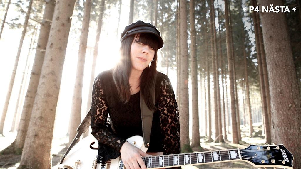 kvinna i svarta kläder och basker utomhus i skogen med en gitarr