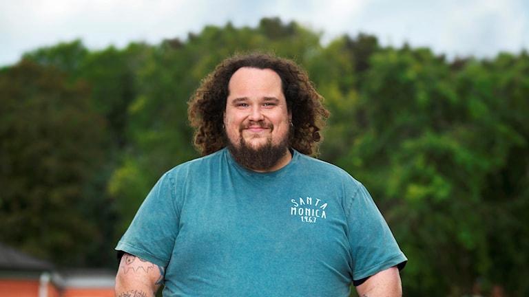 Man med lockigt halvlångt mörkt hår och skägg i ljusblå t-shirt med en bakgrund av träd.