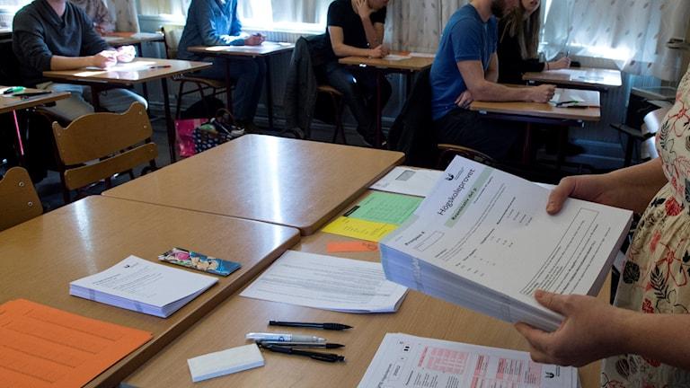 En provvakt delar ut högskoleprov till personer som sitter i skolbänkar. Foto: Bertil Enevåg Ericson/TT