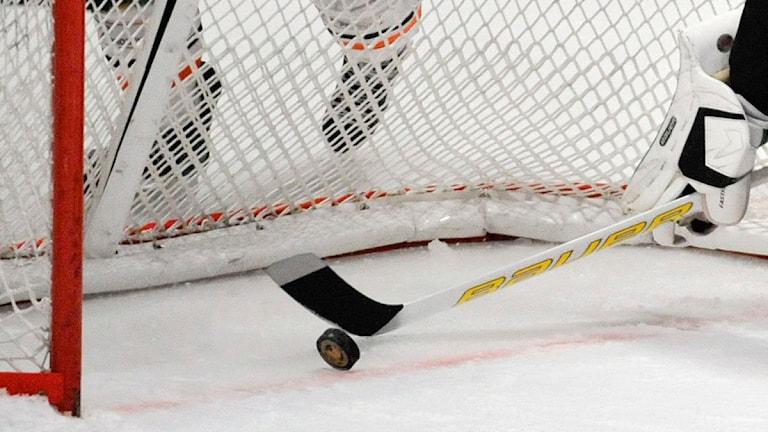 Hockeyklubba och puck i mål