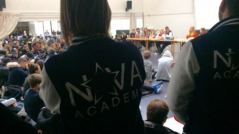 Två elever med jackor med skolans logotyp står framför et stor samling elever i skolsal.
