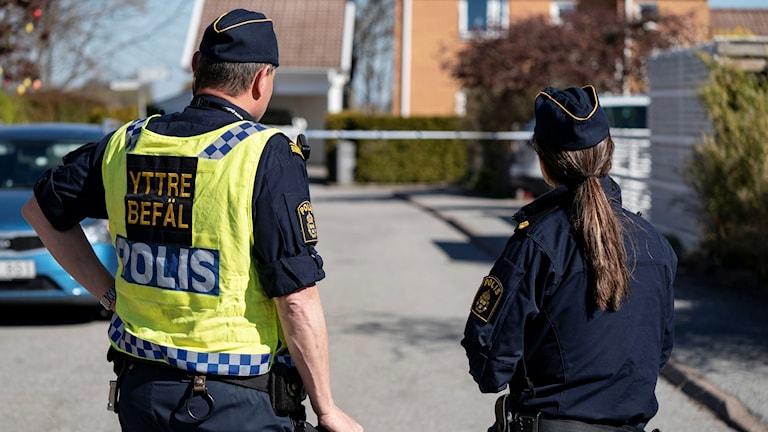 Två poliser framför en avspärrning med tejp