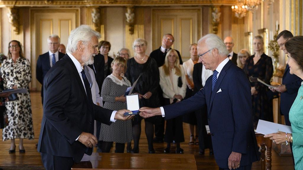 Två äldre män står vända mot varandra och den ene ger den andre en medalj.