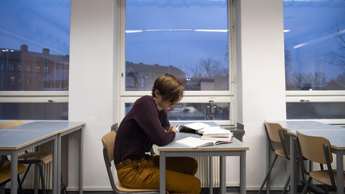 Person sitter ensam vid skolbänk och stirrar ned på papper och böcker. Rummet ser tomt ut i övrigt och utanför fönstret syns kvällshimlen