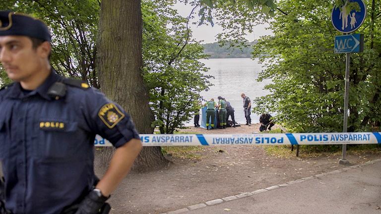 Polis och ambulanspersonal vid en strand där en person befaras ha drunknat.
